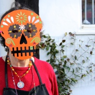 Woman wearing a day of the dead skull mask outside the studios