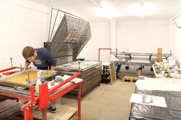 Screen printing studio with vacuum bed tables and drying rack